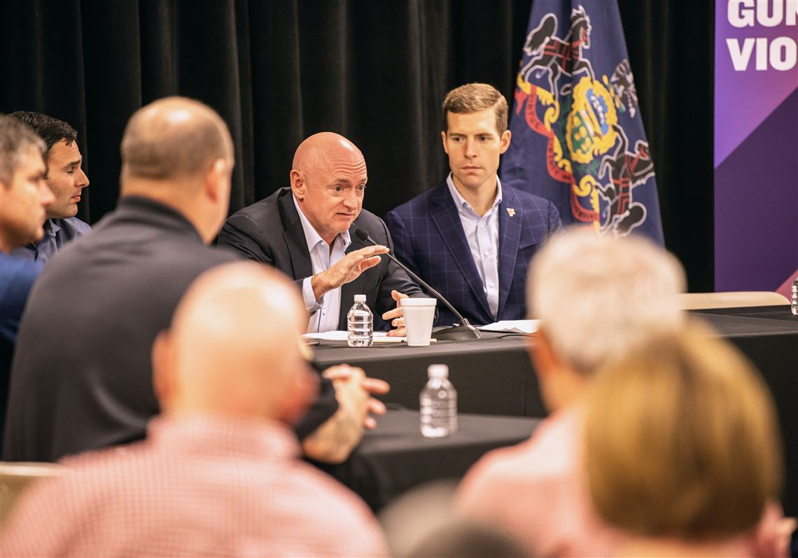 Capt. Mark Kelly, center, speaks about his experience with gun violence as U.S. Rep. Connor Lamb, right, listens, during a community panel discussion on gun violence Saturday at the Heidelberg Volunteer Fire Department.