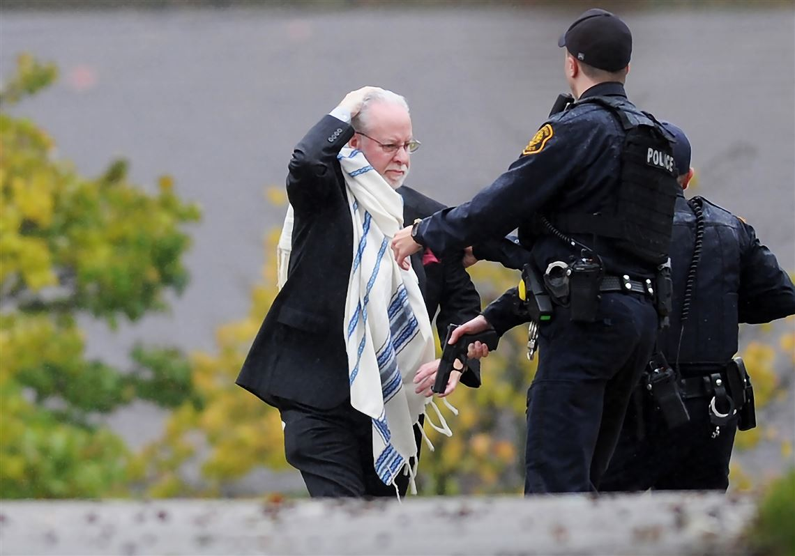 A man holds his head as he is escorted out of the synagogue by police on e52675e6a
