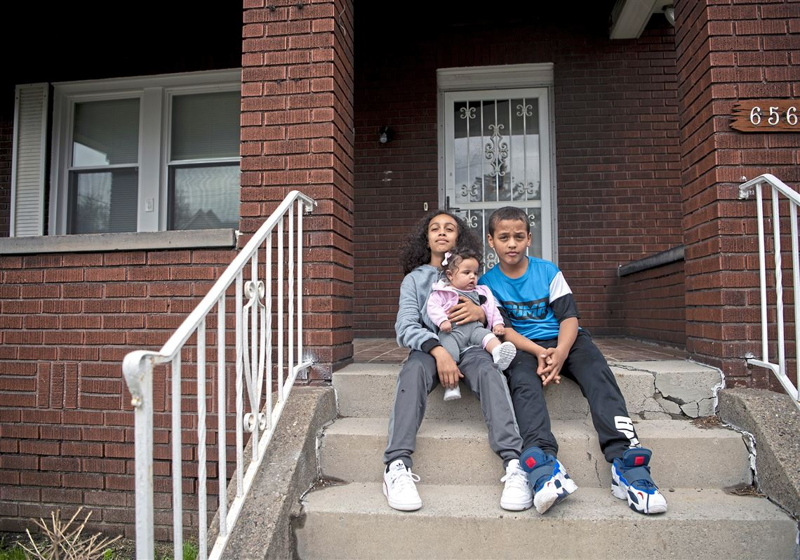 William, Zyiah, and Devontae Thompson, 11, 5 months, and 9, sit outside of their home in Bellevue, in this photo from April 2019. Their home was renovated under the Lead Safe Homes program, which included changes to the windows and front door.