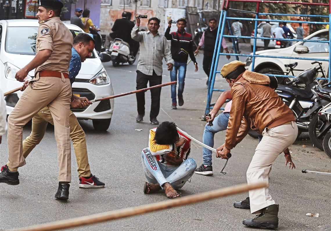 Police officers baton-charge a man during a protest against a new citizenship law in Ahmadabad, India, on Dec. 19, 2019.