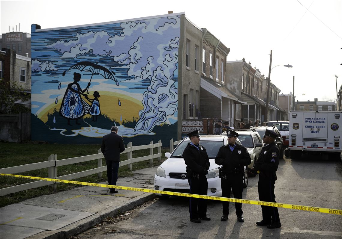 Police gather at the scene of a fatal shooting in the center row home in  Philadelphia