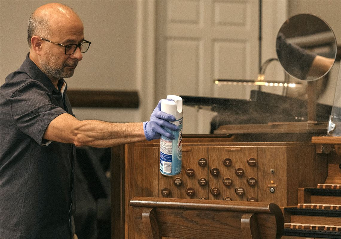 A member of Independent Presbyterian Church sprays an organ with Lysol to take precautions against the spread of the coronavirus at Independent Presbyterian Church in Memphis, Tenn., on March 29, 2020.