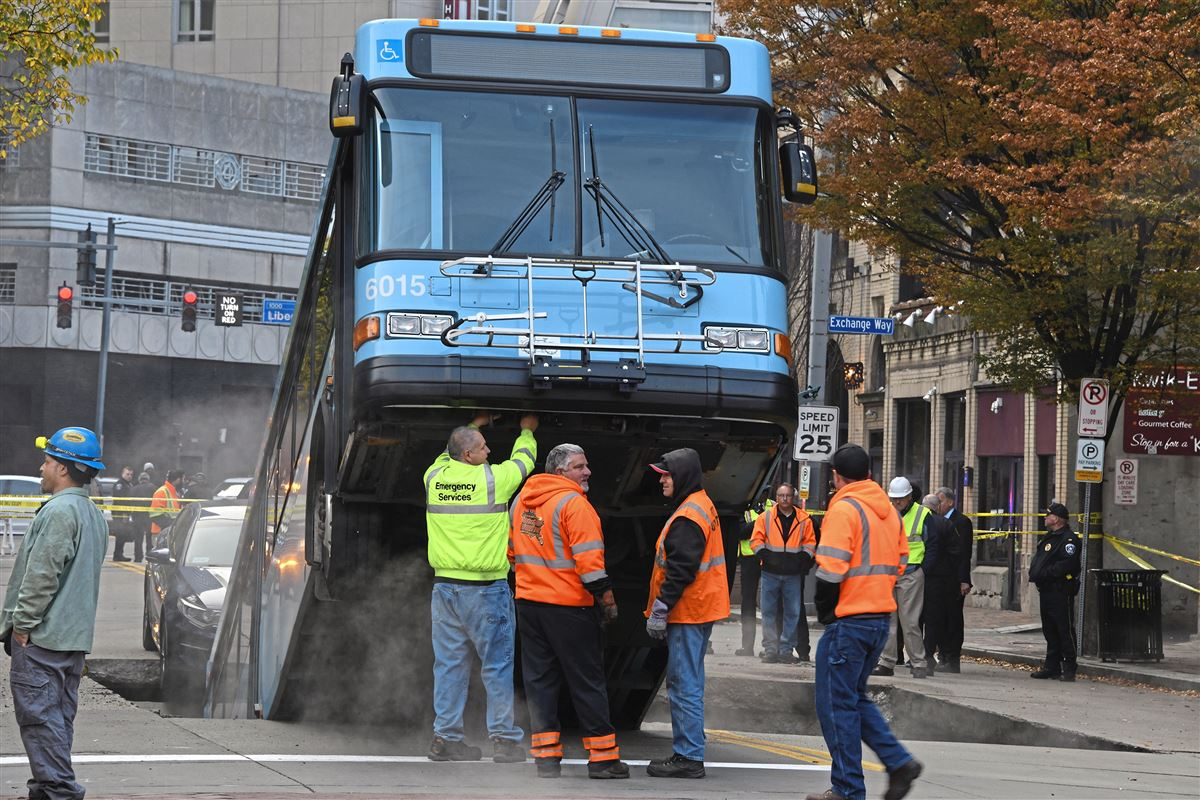 Pittsburgh port authority bus projecting upward from a sinkhole in the middle of a downtown street