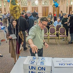 Tom McWhorter, a University of Pittsburgh lecturer and the Department of English's academic integrity officer, drops a union card into a ballot box at the William Pitt Union on Jan. 22, 2018.