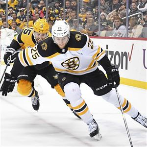 Penguins center Riley Sheahan battles for loose puck with Bruins defenseman  Brandon Carlo Friday Dec. 6bb7dd2fd