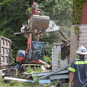 Jadell Minniefield of Hazelwood, owner of Jadell Minnifield Construction Services Inc., left, operates an excavator as he works to demolish an abandoned home, which has recently tested positive for lead contamination, while employee Roger Marva of Hazelwood, right, watches from the road, Tuesday, July 2, 2019, in Braddock Hills.